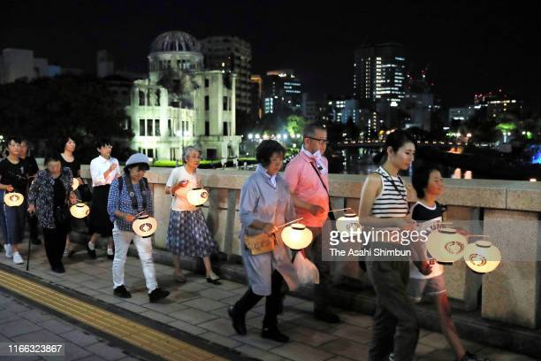 People march on in front of illuminated Atomic Bomb Dome at the Hiroshima Peace Memorial Park on August 5 2019 in Hiroshima Japan Japan is preparing...