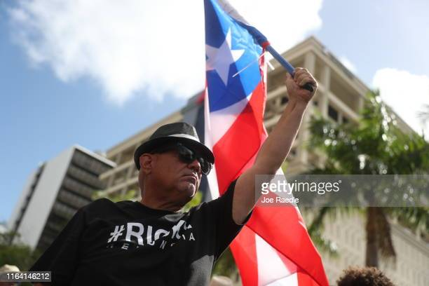 People march through the financial district as they celebrate the ouster of Ricardo Rossello the Governor of Puerto Rico on July 25 2019 in Old San...