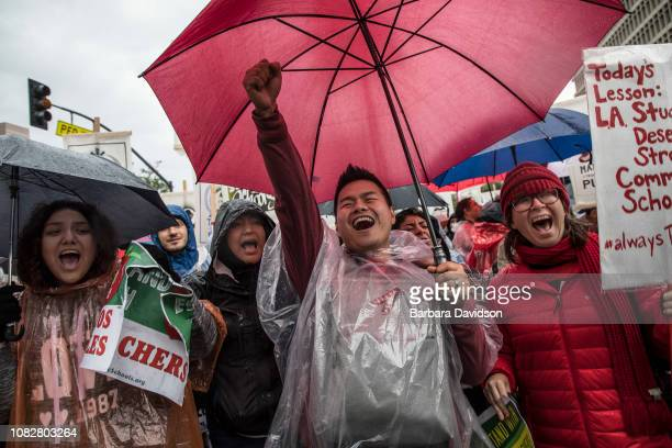 People march through the streets of downtown in the pouring rain during a United Teachers Los Angeles strike on January 14 2019 in Los Angeles...