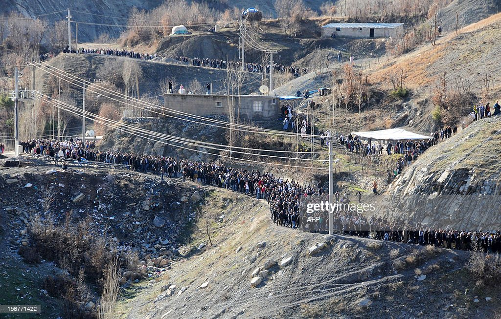 People march to the cemetery of Gulyazi village on December 28, 2012 on the first anniversary of a Turkish military air strike aimed at Kurdish rebels that killed 34 civilians working as smugglers at the Turkey-Iraq border in Sirnak.