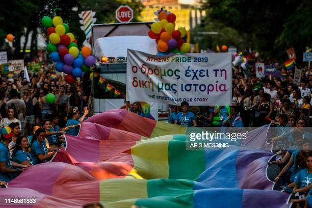 People march with a large rainbow flag as they take part in the Athens Gay Pride in Athens on June 8 2019 Thousands marched in the 15th annual Athens...