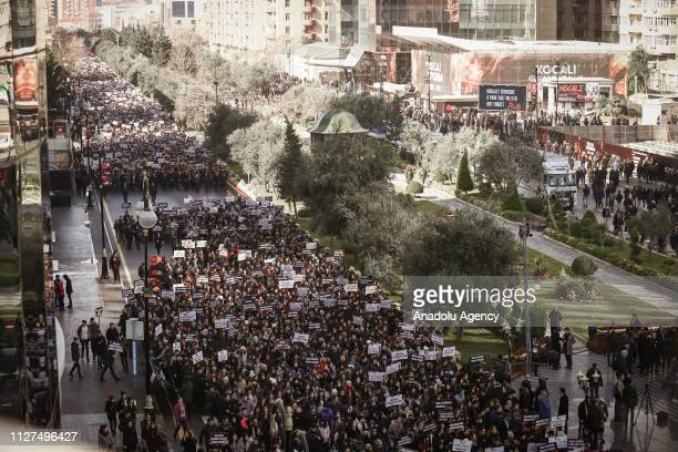 People march with banners towards 'Khojaly Genocide Memorial' on the 27th anniversary of 'Khojaly Massacre' in Baku Azerbaijan on February 26 2019...
