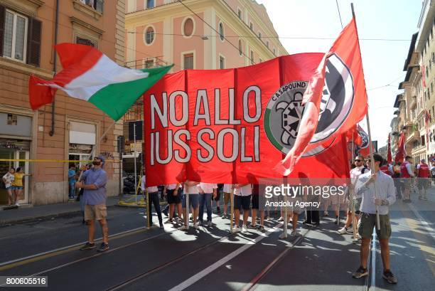 People march with flags and a banner that translates No to Jus Soli during a protest against the law on Jus Soli which would give birthright...