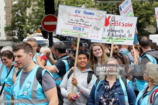 People march with placards reading In France 6 million deaf people refused TV news for lack of subtitles Are we invisible and Need for an interpreter...