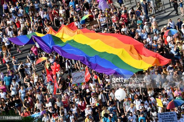 People march with their giant rainbow flag from the parliament building in Budapest downtown during the lesbian, gay, bisexual and transgender Pride...