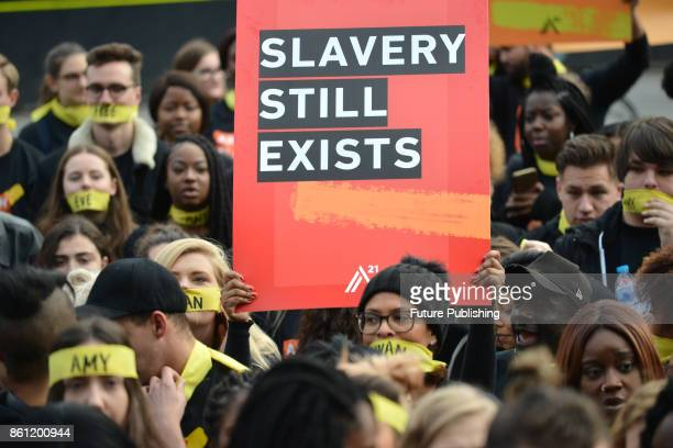 People marching against modern slavery through London wearing face masks representing the silence of modern slaves in forced labour and sexual...