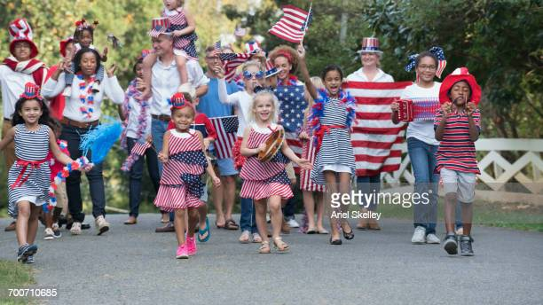 people marching in 4th of july parade in park - independence day stock pictures, royalty-free photos & images