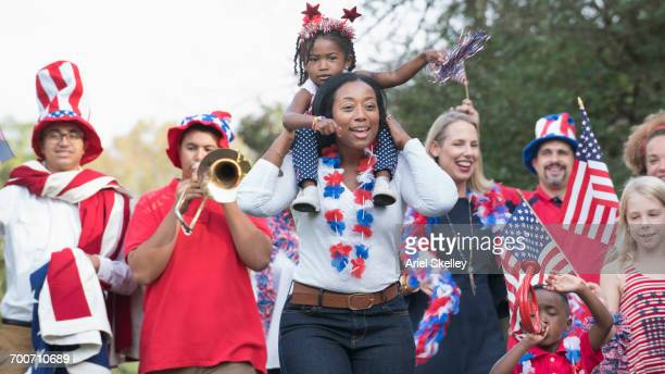 people marching in 4th of july parade in park - marching stock pictures, royalty-free photos & images