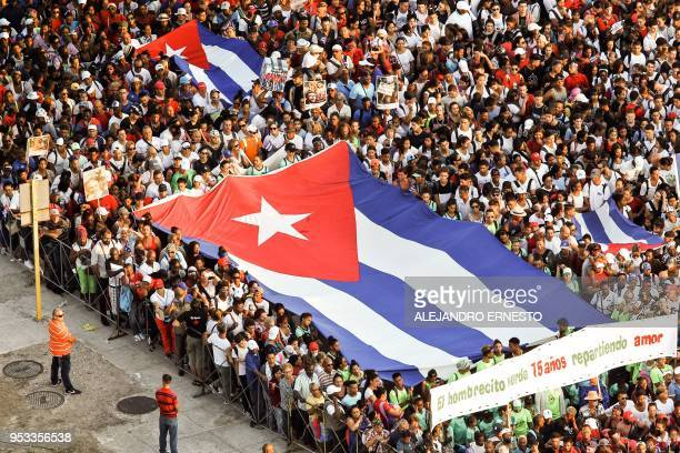 People marching to celebrate May Day display Cuban flags as they arrive at Revolution Square in Havana on May 1 2018