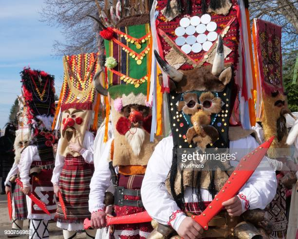 People masked as a 'Kukeri' show their ritual dance masks during a three days open festival called 'Masquerade Games of Dobrudzha' in the village of...