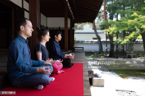 3 people meditating in temple garden - japanese culture stock pictures, royalty-free photos & images