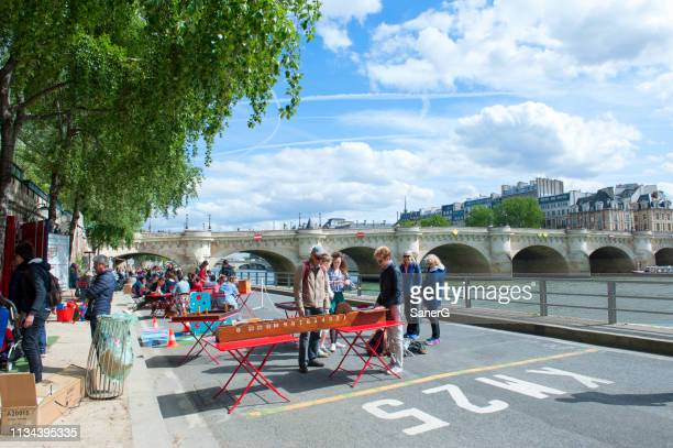 people meeting for play games on the quay along the seine river in paris - quayside stock pictures, royalty-free photos & images