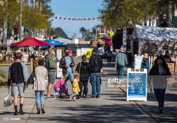 People mill about on Main St. On Tuesday, March 16, 2021 in Ventura, CA.