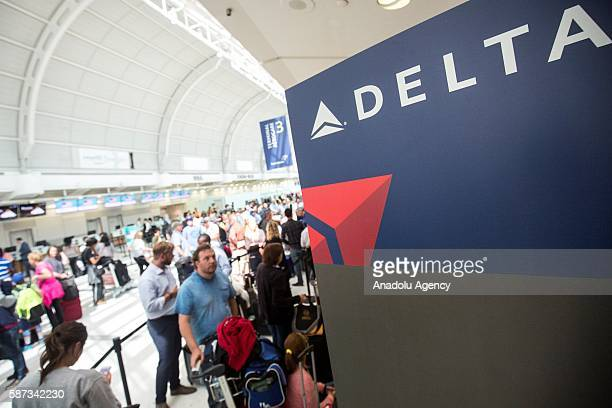 People mill around while passengers await updates from Delta airline employees at Pearson International airport in Toronto Canada on August 8 2016...