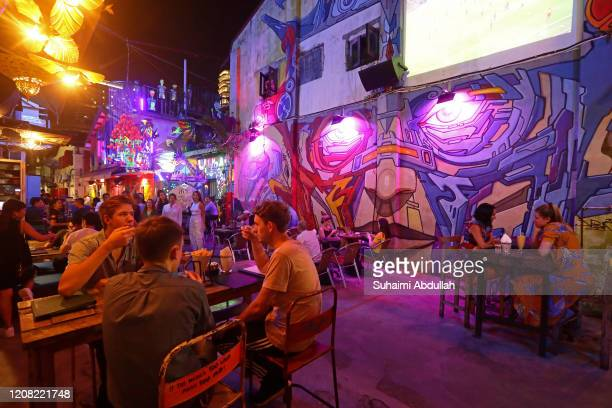 People mingle over food and drinks at a restaurant on March 25, 2020 in Singapore. The Singapore government is set to close all entertainment outlets...