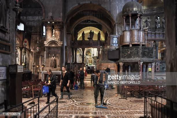 People mop the floor of the flooded St Mark's Basilica after an exceptional overnight Alta Acqua high tide water level on November 13 2019 in Venice...