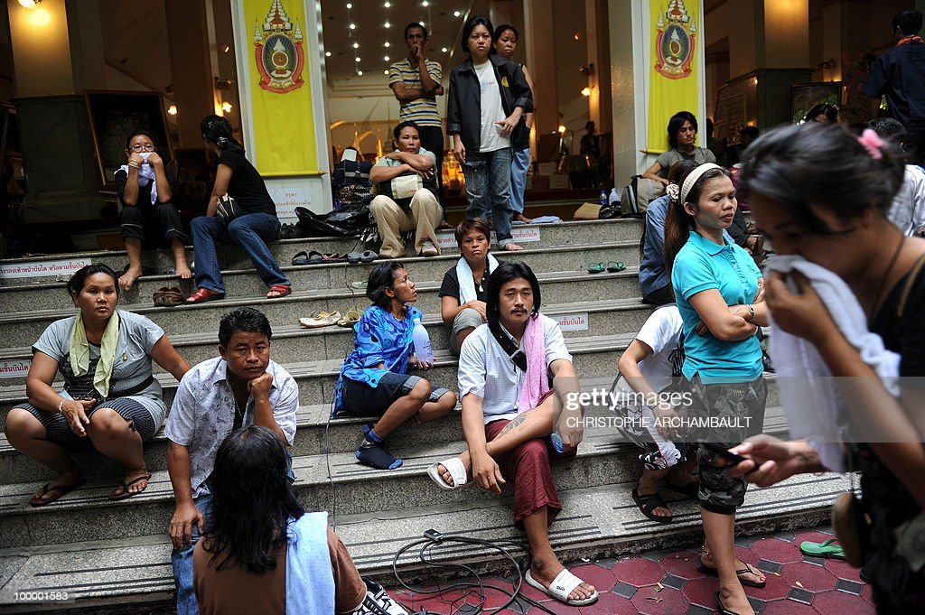 People, most of them who had gathered at a temple which had been turned into a shelter within an anti-government protest site, sit on the stairs of a temple beside the dead bodies of anti-government protestors killed in a gunbattle the day before, in downtown Bangkok on May 20, 2010. Gunshots rang out near a Buddhist temple in the heart of an anti-government protest zone in Bangkok, and soldiers were advancing on foot along an elevated train track, an AFP photographer saw. Thai security forces stormed the 'Red Shirts' protest camp on May 19 in a bloody assault that forced the surrender of the movement's leaders who asked their supporters to disperse. AFP PHOTO/Christophe ARCHAMBAULT