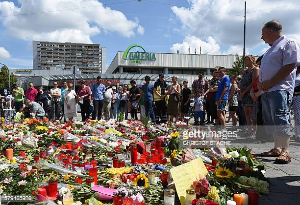 People mourn at a memorial of candles and flowers on July 24 2016 in front of the Olympia Einkaufszentrum shopping centre in Munich southern Germany...