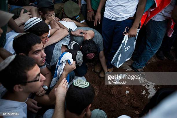 People mourn by the graves during the funeral ceremony held for the three Israeli teenagers found dead on July 1 2014 in Modiin Israel The bodies of...