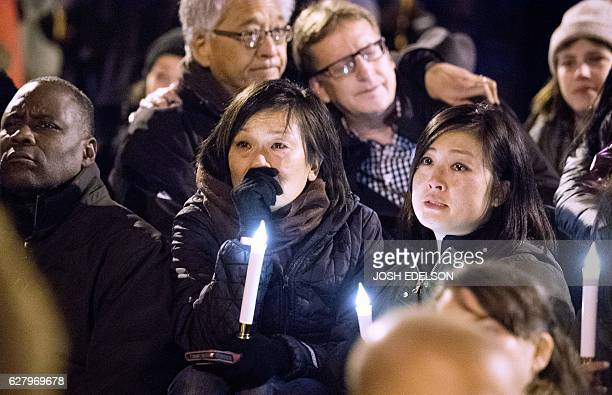 People mourn during a vigil honoring those who died in a warehouse fire in Oakland California on December 5 2016 The death toll from the massive...