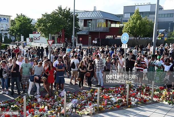 People mourn in front of candles and flowers on July 24 2016 in front of the Olympia Einkaufszentrum shopping centre in Munich southern Germany where...