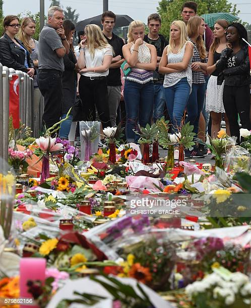People mourn in front of candles and flowers on July 25 2016 in front of the Olympia shopping mall in Munich southern Germany where an 18yearold...