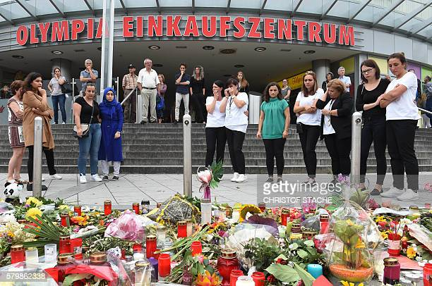 People mourn in front of candles and flowers on July 25 2016 near the Olympia shopping mall in Munich southern Germany where an 18yearold...