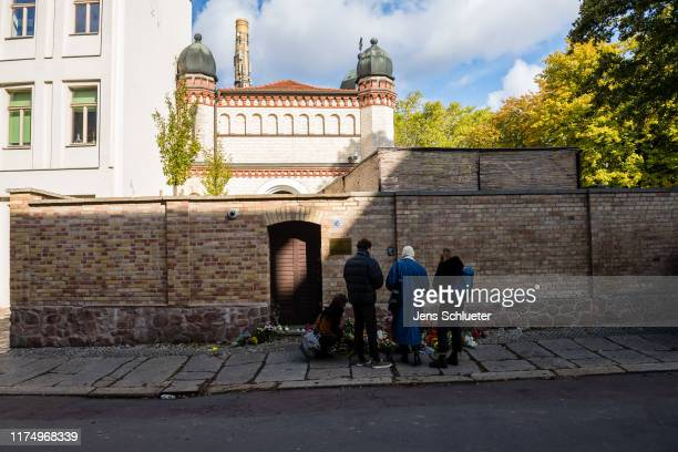 People mourn in front of the entrance to the Jewish synagogue on October 10, 2019 in Halle, Germany. Law enforcement authorities, after initially...