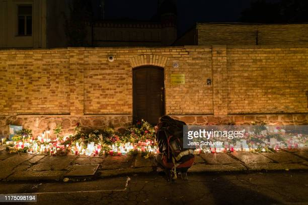 People mourn in front of the entrance to the Jewish synagogue on October 10 2019 in Halle Germany Law enforcement authorities after initially...