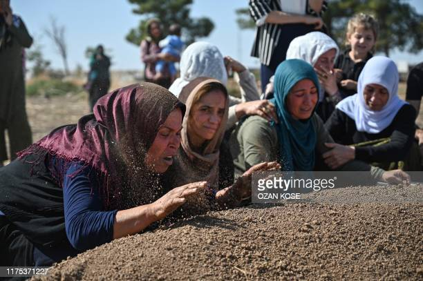 People mourn in front of the grave of Halil Yagmur who was killed in a mortar attack a day earlier in Suruc near northern Syria border, during...