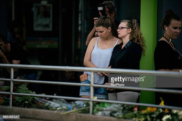 People mourn near the crime scene and lay flowers outside the OEZ shopping center the day after a shooting spree left nine victims dead on July 23...
