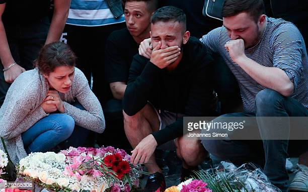 People mourn near the crime scene at OEZ shopping center the day after a shooting spree left nine victims dead on July 23 2016 in Munich Germany...