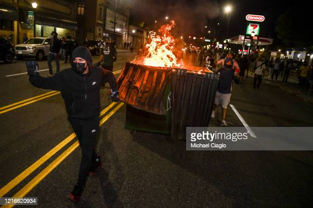 People move a burning dumpster toward a line of police officers during the fourth consecutive day of protests on May 31, 2020 in Denver, Colorado....