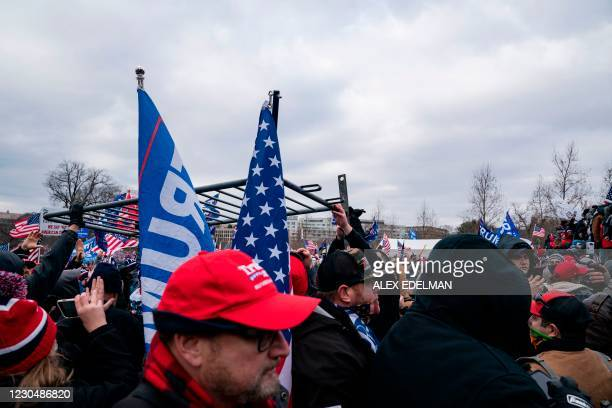 People move a security barrier as supporters of US President Donald Trump protest outside the US Capitol on January 6 in Washington, DC. - Donald...