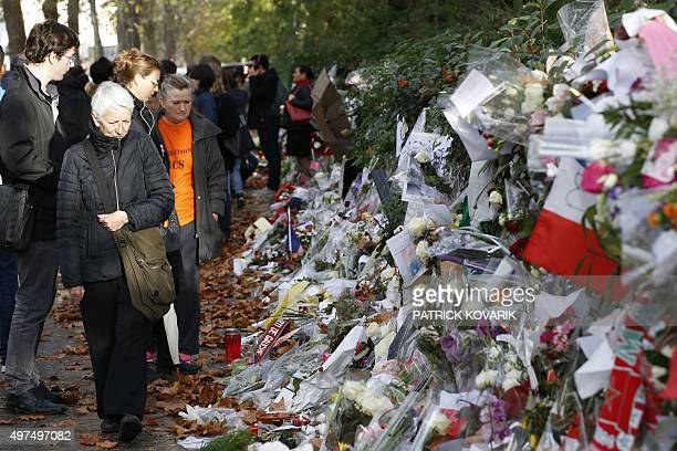 People move past floral tributes laid near the Bataclan Theater in Paris on November 17 where at least 82 people were killed during coordinated...