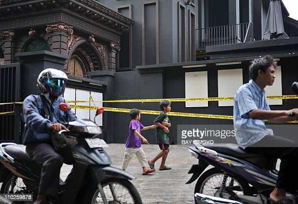 People move past police tape securing the residence of Indonesian rock musician Ahmad Dhani who is known for his songs protesting against religious...