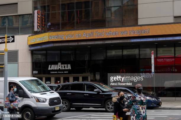 """People move past the Regal Cinemas marquee that reads, """"look forward to seeing you on April 2nd when we reopen!"""" at the Regal cinemas in Union Square..."""