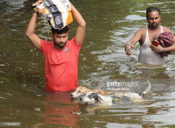 People move to safety with a couple of dogs on the sixth day of water logging after heavy rain at Rajendra Nagar on October 3 2019 in Patna India The...