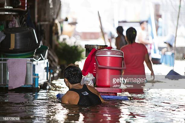 CONTENT] people moving their belongings to a dry place inside a flooded market in Yai district of Bangkok Thailand on the Thonburi west bank of the...