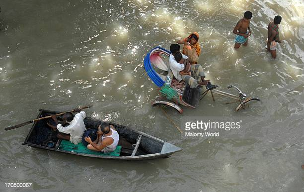 People moving through the flood waters in Sirajganj town one of the worst flood affected areas in Bangladesh The embankment built to protect the city...