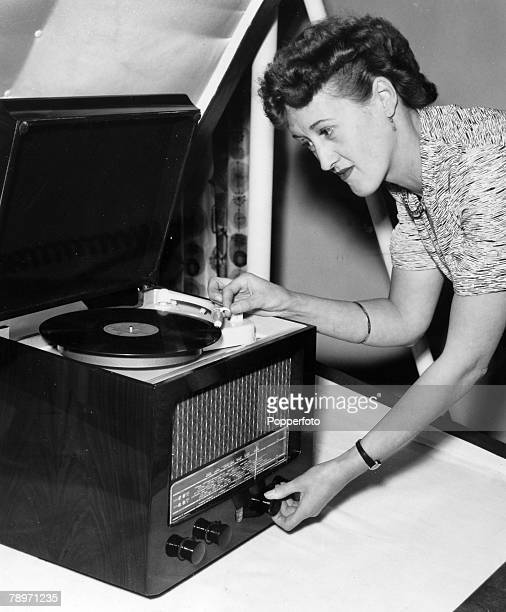 1954 London A woman plays a 12 inch record on a Phillips miniature table radiogram