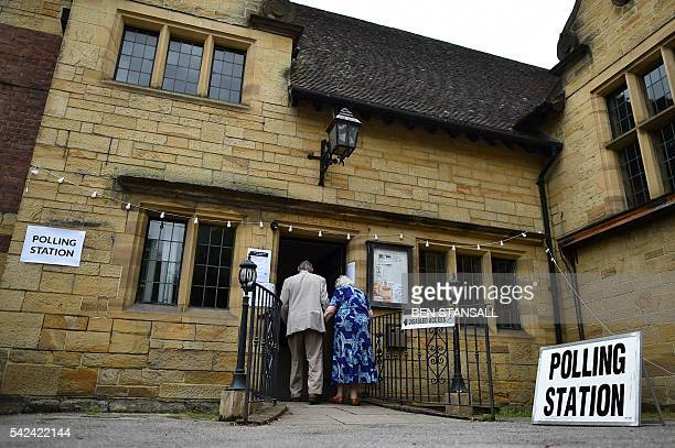 People narrive to cast their ballots at a polling station set up in a village hall in Penshurst southeast of London on June 23 as Britain holds a...