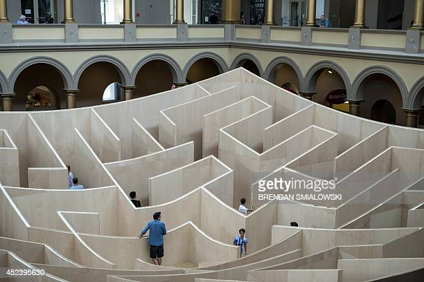 People navigate a maze at the National Building Museum July 19 2014 in Washington DC AFP PHOTO/Brendan SMIALOWSKI