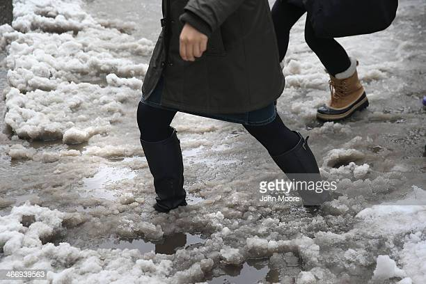 People navigate a slushy intersection near Union Square on February 5 2014 in New York City United States New Yorkers like millions of Americans in...