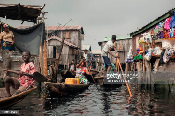 People navigate the the waterways of Makoko waterfront community in Lagos on May 15, 2018. - Members of various waterfront communities and the...