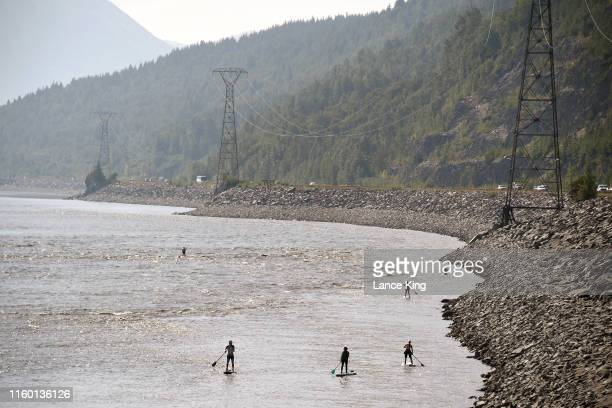 People navigate the Turnagain Arm on paddle boards as vehicles move along the Seward Highway on July 4 2019 south of Anchorage Alaska Alaska is...