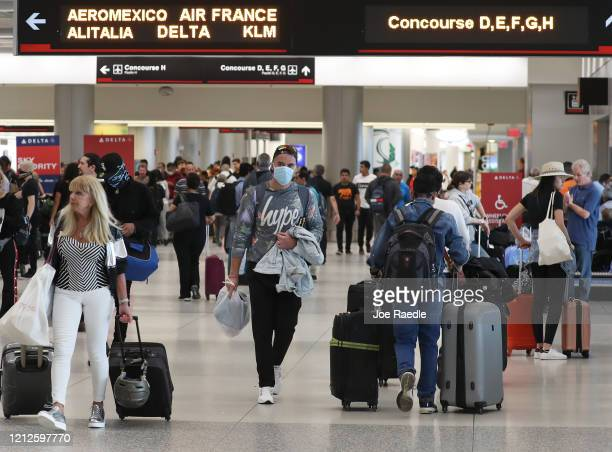 People navigate through Miami International Airport amid coronavirus fears on March 15 2020 in Miami Florida Airline companies have seen travelers...