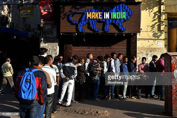 People near a 'Make in India' sign wait for a State Bank of India branch to open in Delhi India on Friday Nov 25 2016 India's government is grappling...