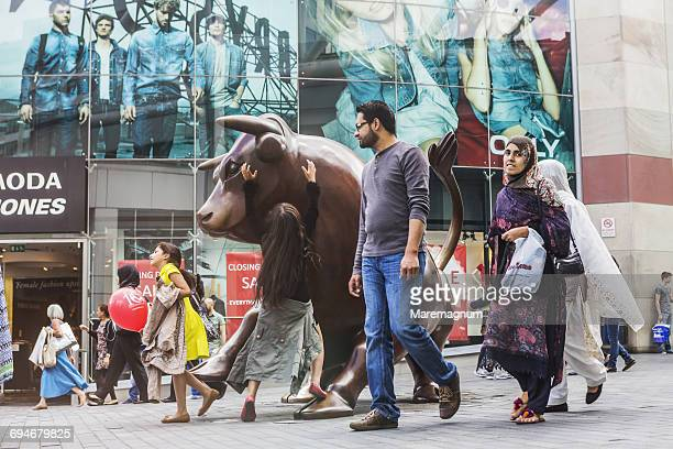 People near the bronze bull (The Guardian)