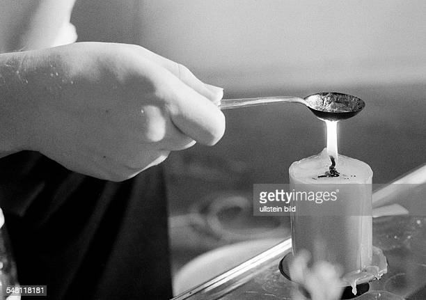 People, night of New Years Eve, celebrating New Years, symbolic, soothsay, lead-pouring, hand holds a spoon containing plumb over a lighted candle -